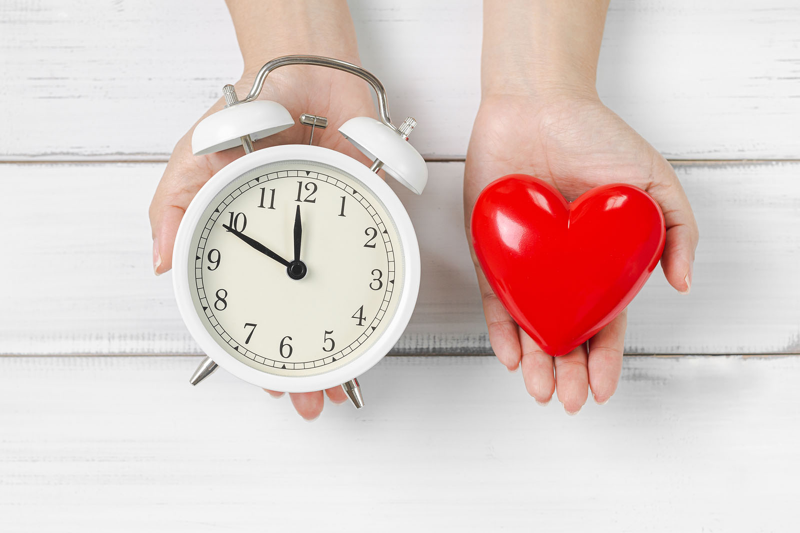 Woman Hands Hold Alarm Clock and Red Heart on white wood background